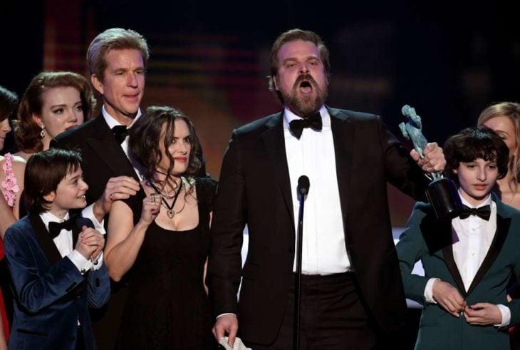 personas en microfono recbiendo premio