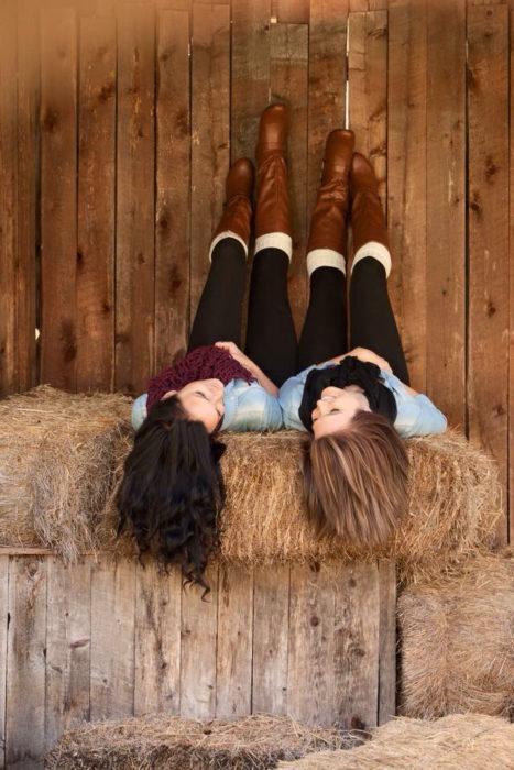 Chicas recostadas sobre paja conversando