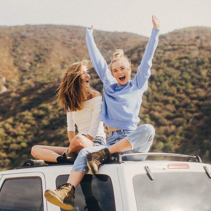 Chicas sobre una camioneta levantando los brazos y riendo