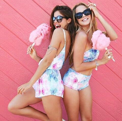 Chicas comiendo algodones de azucar mientras están recargadas una sobre la otra