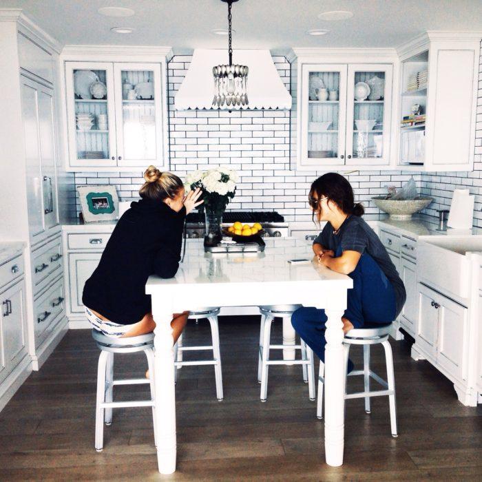Chicas sentadas en la cocina hablando