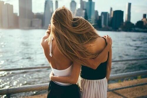 Chicas abrazadas mientras miran el mar