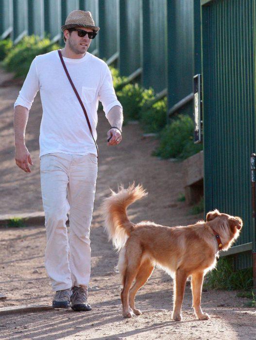 hombre con playera blanca y perro