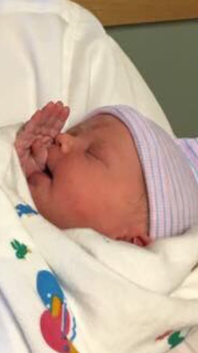 Bebé saludando con su pequeña mano