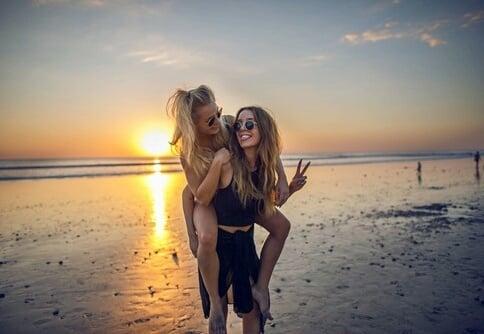 amiga cargando a su amiga en la playa