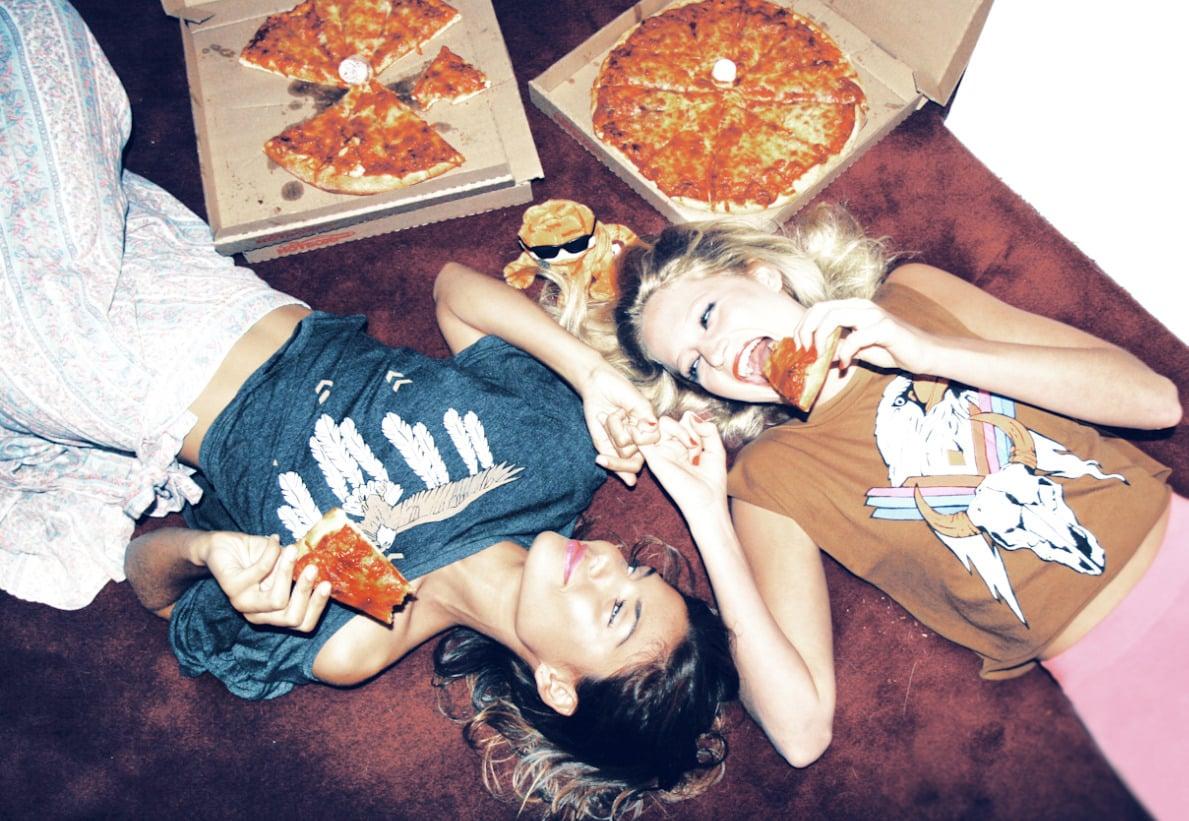 amigas acostadas comiendo pizza