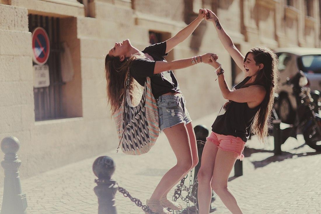 amigas jugando en una cadena por la calle