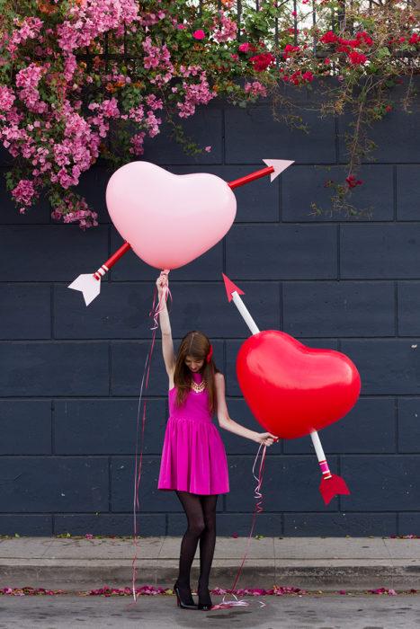 mujer con globos grandes en forma de corazones flechados