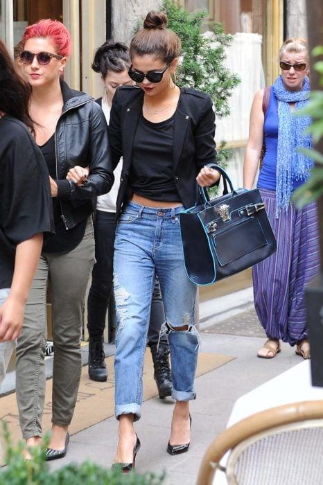 mujer con jeans rotos y chaqueta