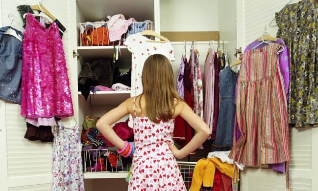 una joven observando el desorden en su armario