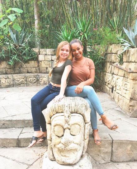 Chica junto a su madre sentadas en una piedra
