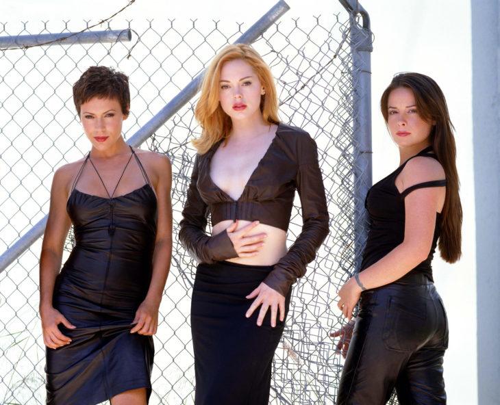 tres mujeres de pie en una reja