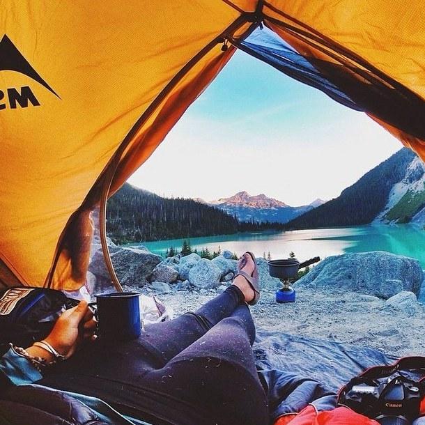 chica acampando sosteniendo una taza
