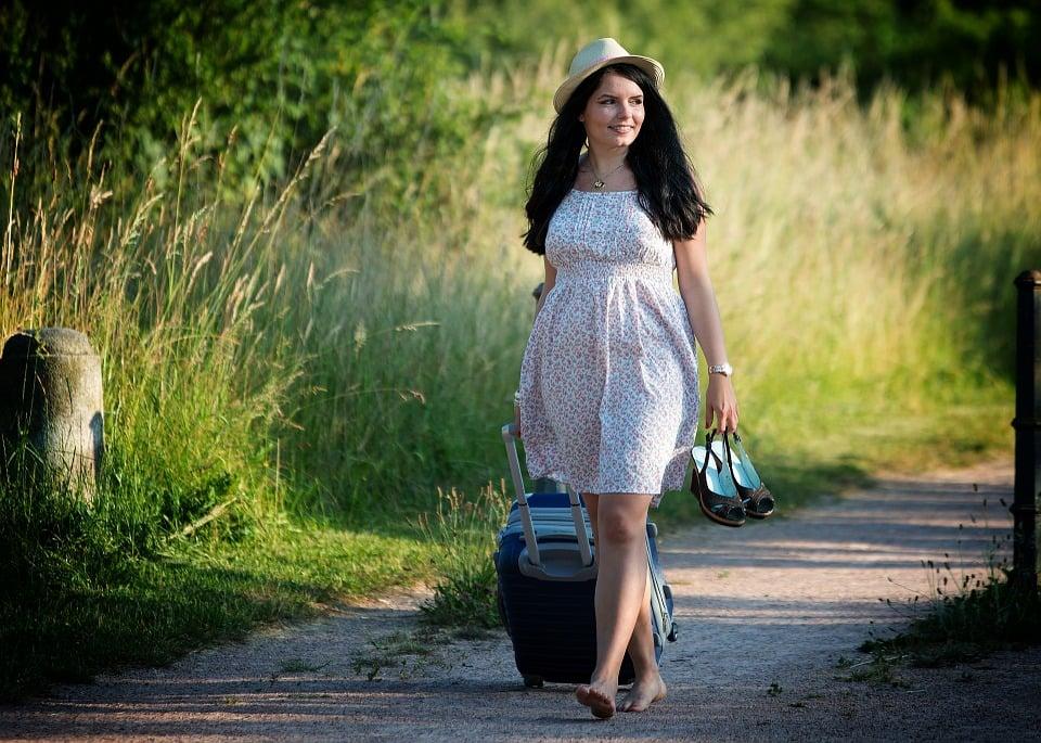 chica caminando por el sendero con una maleta