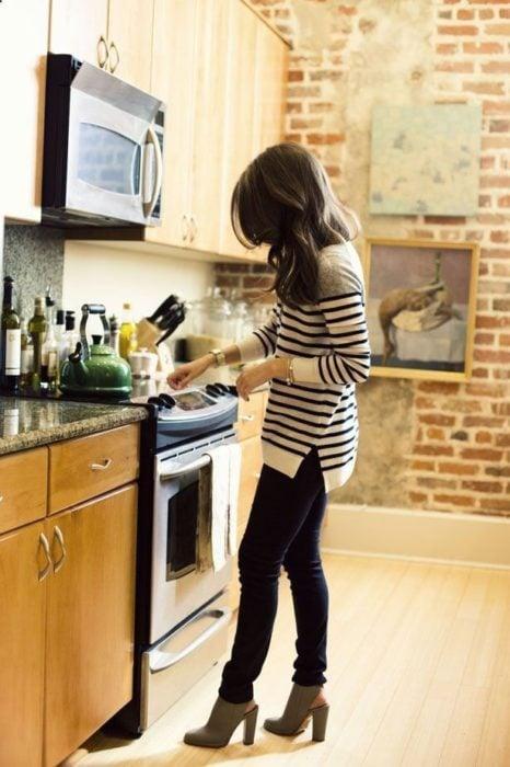 chica cocinando con pantalón negro y blusa de rayas
