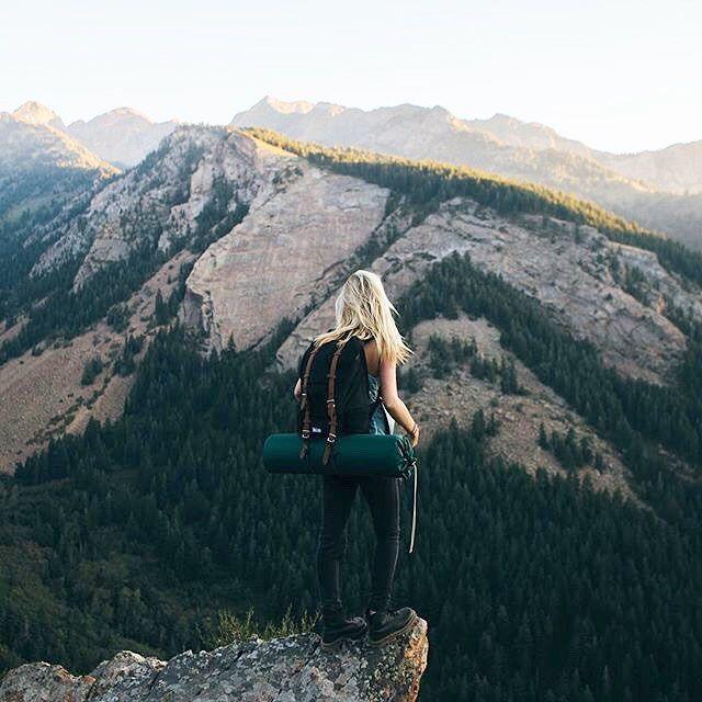 chica en la cima de una montaña con su equipo para acampar