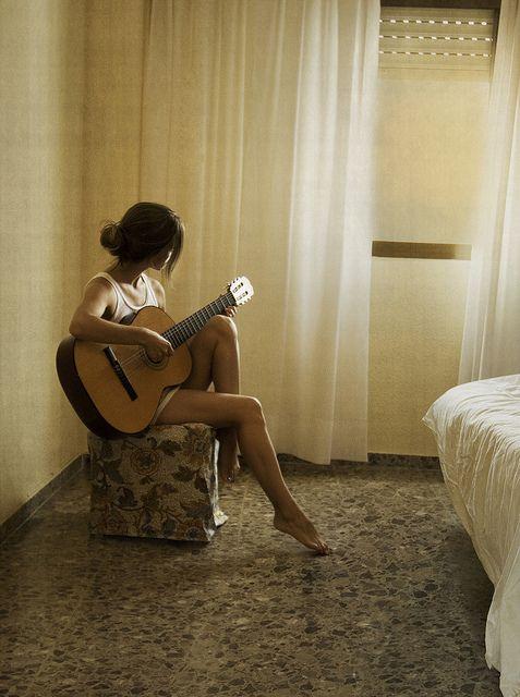 chica tocando la guitarra en su habitación