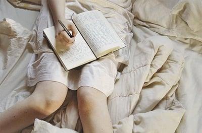 chica escribiendo en su diario sobre su cama