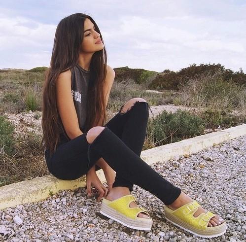 chica sentada al lado del camino