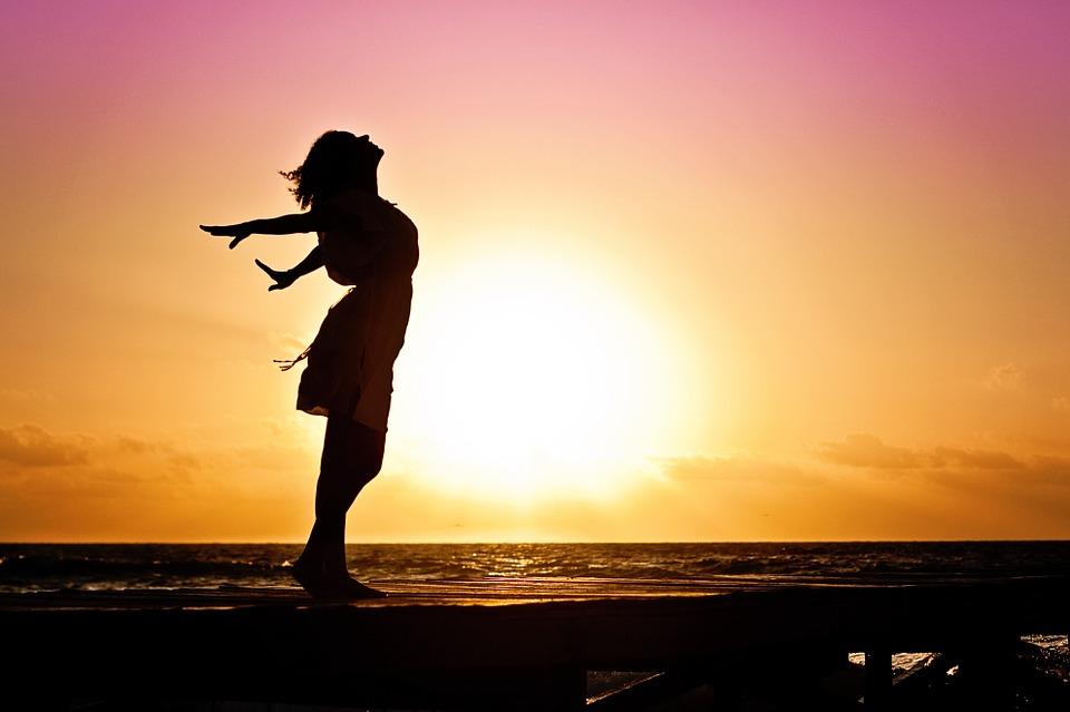 chica feliz viendo el atardecer en el mar
