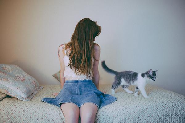 chica introvertida con gato sentada sobre la cama