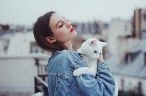 chica introvertida con su gato blanco en el balcón