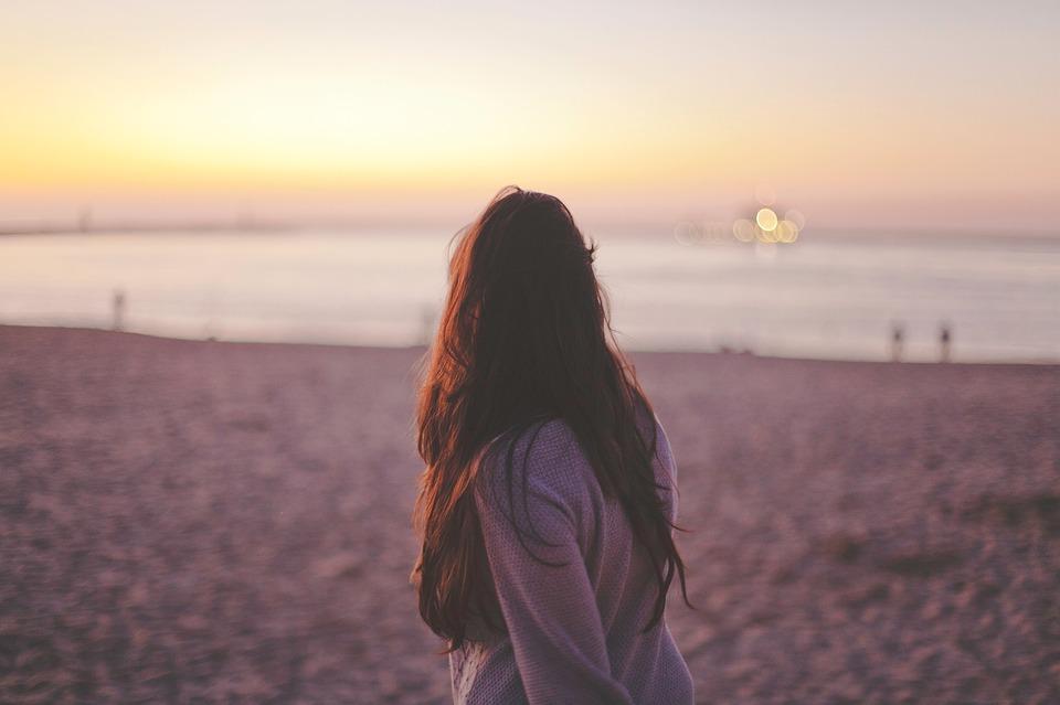 chica mirando el mar desde la playa