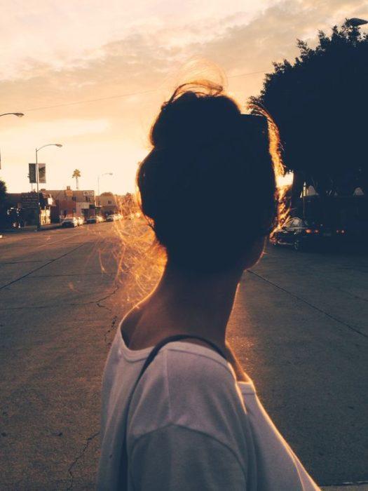 Chica observando el atardecer en la ciudad