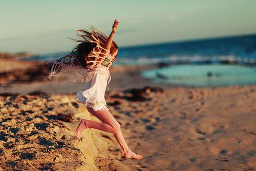 chica saltando en la arena