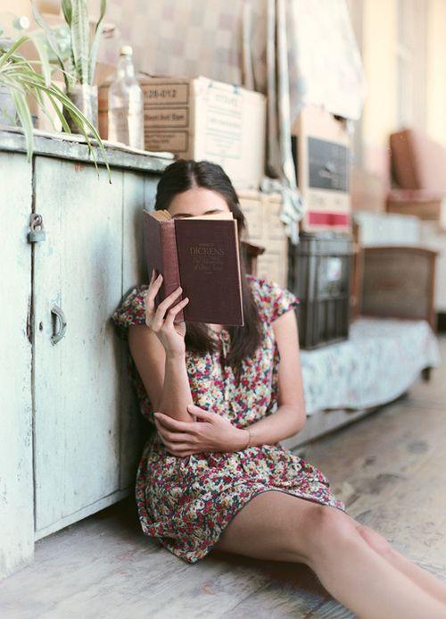 chica senada en el piso leyendo a dickens