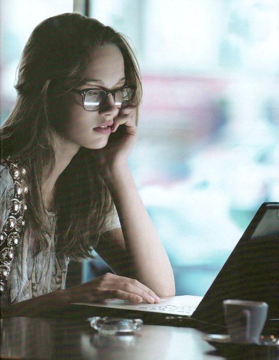 chica con lentes pasando su tiempo con su computadora editada