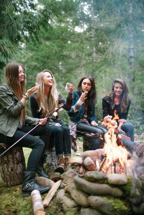 chicas asando bombones en una fogata