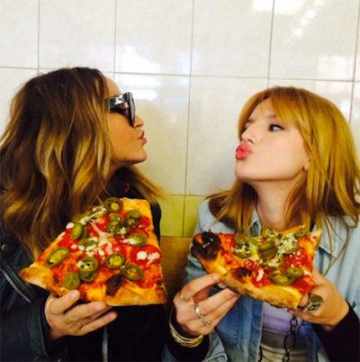 dos chicas comiendo pizza muy condimentada