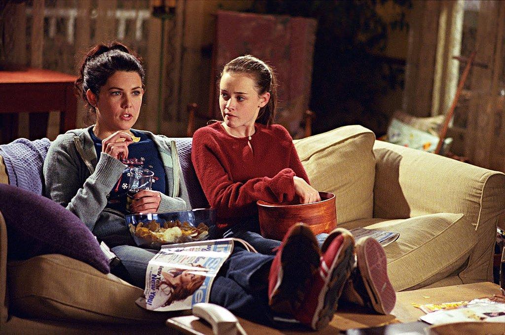 chicas viendo la televisión sentadas en sofa comiendo palomitas