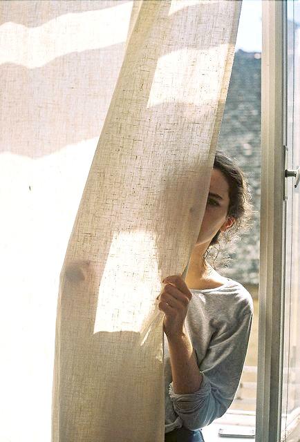 chica tras una cortina luz