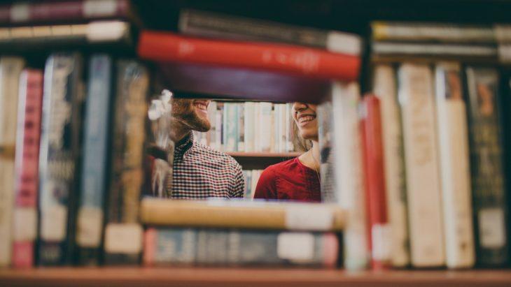 chica hablando con chico en la biblioteca