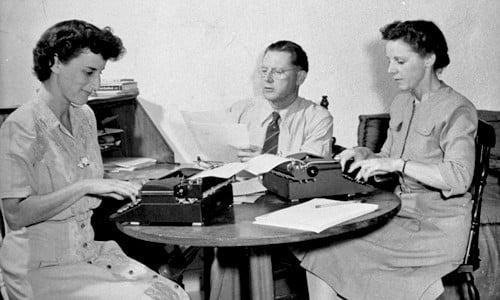 dos secretarias escribiendo en maquina de escribir con su jefe