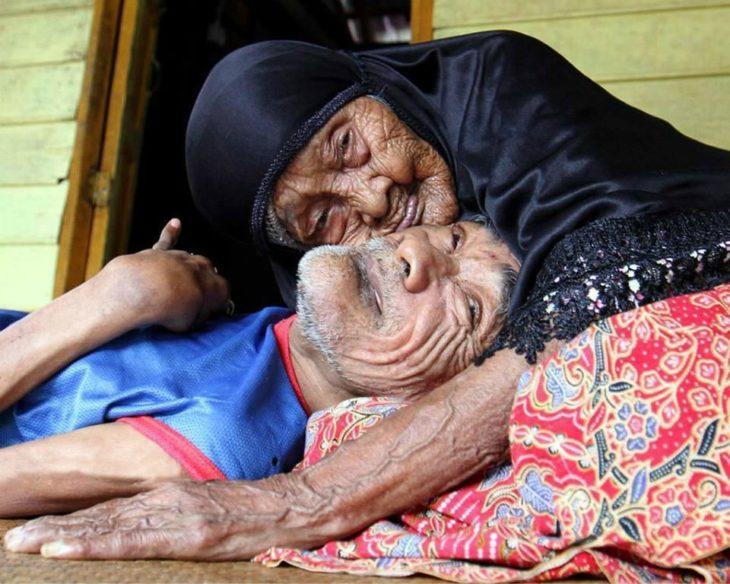 mujer anciana abraza a hombre en el suelo