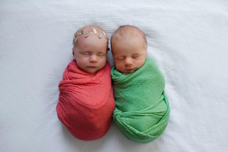 bebés recién nacidos envueltos en cobijas verde y rosa
