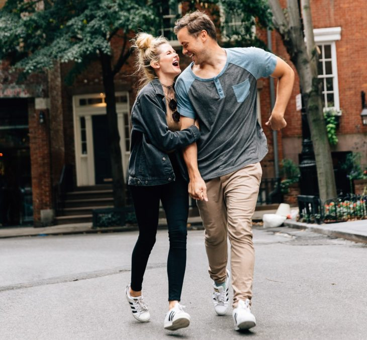 hombre y mujer abrazados caminando por la calle