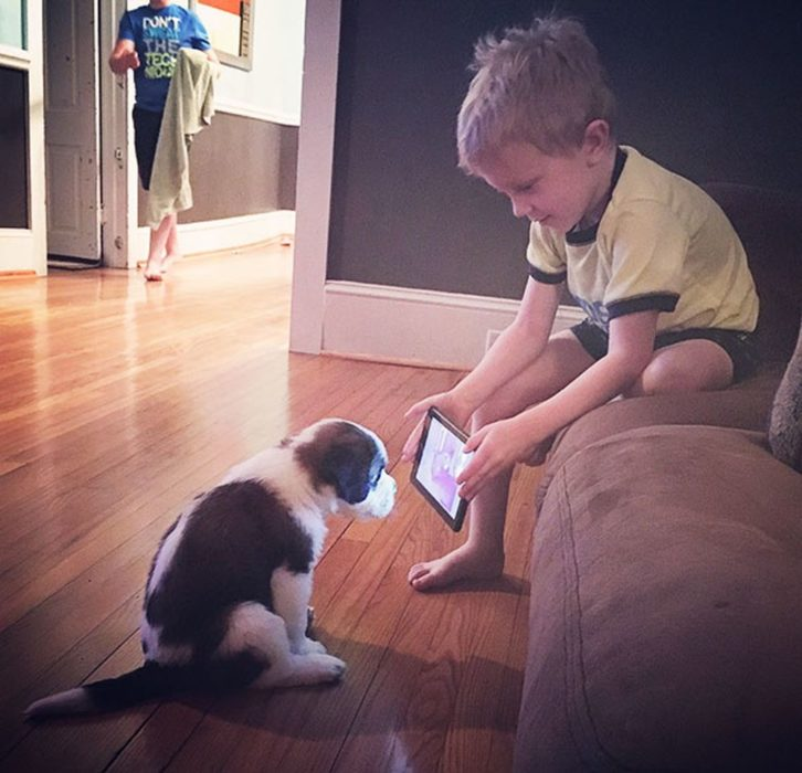 niño con tablet y perro