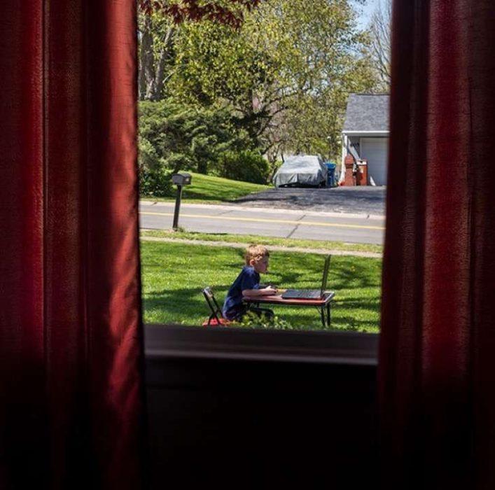 niño jugando con laptop en el jardin