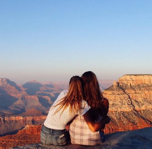 Chicas sentadas viendo el gran cañón
