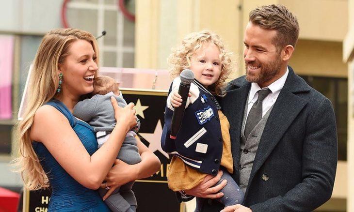 hombre y mujer rubia cargando a niñas con microfono