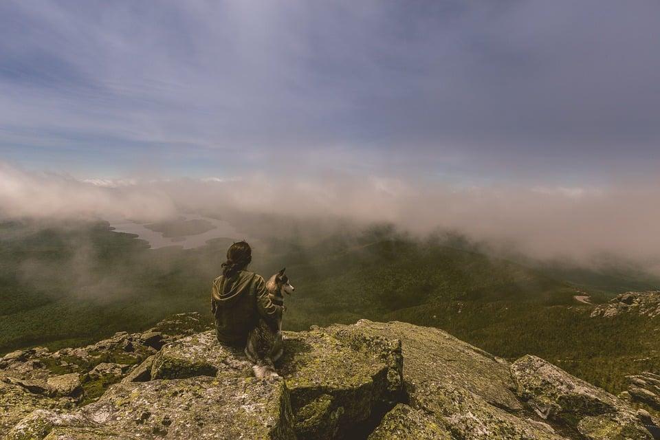 mujer con su perro frente a un paisaje