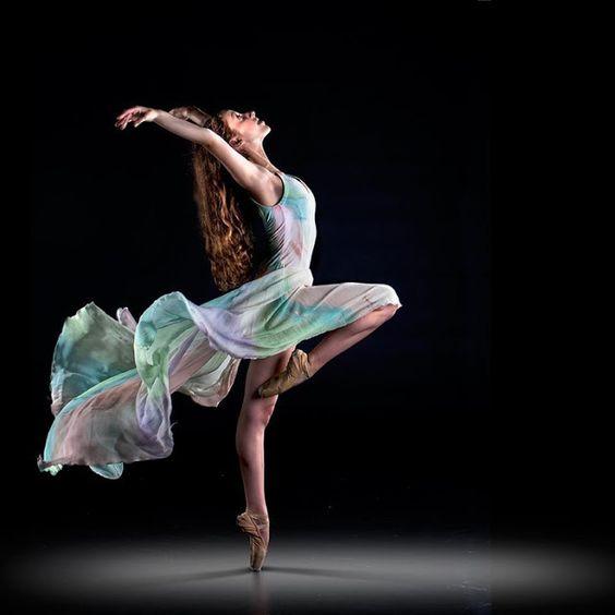 mujer con vestido de colores bailando con fondo oscuro
