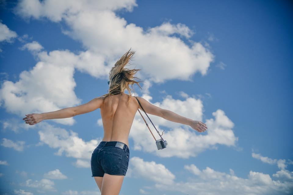 mejer feliz sin playera frente a las nubes y con una camara