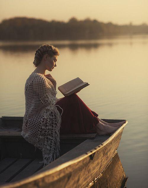mujer leyendo sobre una canoa en el lago
