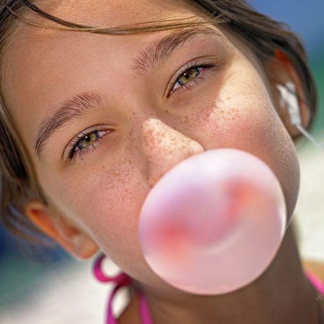 niña con pecas masticando goma de mascar