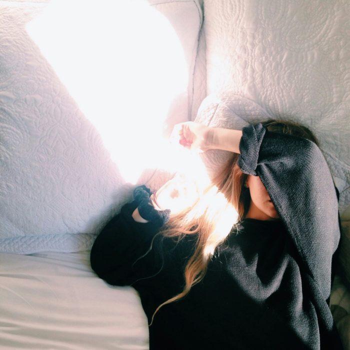 mujer costada en la cama con luz del sol